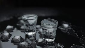 Προσθέστε τους κύβους πάγου στον πυροβολισμό της βότκας στο γυαλί στο μαύρο κλίμα Ποτό οινοπνεύματος φιλμ μικρού μήκους