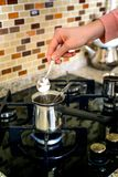 Προσθήκη της ζάχαρης στο δοχείο καφέ στο φούρνο που προετοιμάζει τον τουρκικό καφέ στοκ εικόνες με δικαίωμα ελεύθερης χρήσης