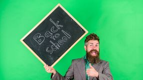 Προσκαλέστε για να γιορταστεί η ημέρα της γνώσης Το γενειοφόρο άτομο δασκάλων κρατά τον πίνακα με την επιγραφή πίσω στο σχολείο π στοκ φωτογραφίες