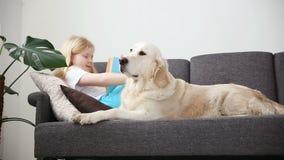 Προσοχή για τα κατοικίδια ζώα Το ξανθό κορίτσι διαβάζει ένα βιβλίο, στον καναπέ με το σκυλί της στο καθιστικό χρυσό ευτυχές retri φιλμ μικρού μήκους