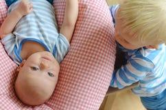 Προσοχή μικρών παιδιών στο νεογέννητο αδελφό του στοκ φωτογραφία