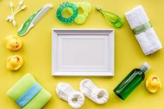 Προσοχή μωρών με το σύνολο, το πλαίσιο, τους νεοσσούς και την πετσέτα λουτρών στο κίτρινο πρότυπο άποψης υποβάθρου τοπ Στοκ Φωτογραφία