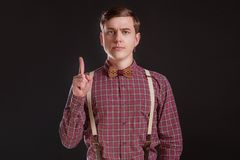 Προσοχή! Ο ακριβής όμορφος νεαρός άνδρας στον εκλεκτής ποιότητας δεσμό τόξων πουκάμισων που κρατά το δάχτυλο αύξησε και που εξετά στοκ φωτογραφίες με δικαίωμα ελεύθερης χρήσης