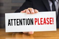 Προσοχή παρακαλώ, μήνυμα στην άσπρη κάρτα και λαβή από τον επιχειρηματία στοκ φωτογραφία