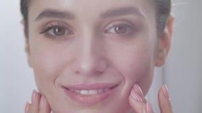 Προσοχή προσώπου Ελκυστική γυναίκα σχετικά με το δέρμα κάτω από την κινηματογράφηση σε πρώτο πλάνο ματιών απόθεμα βίντεο