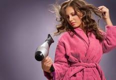Προσοχή τριχώματος Γυναίκα που χρησιμοποιεί το στεγνωτήρα τρίχας για την τρίχα Στοκ Εικόνες