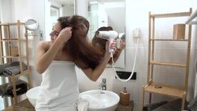 Προσοχή τριχώματος Ξήρανση γυναικών μακρυμάλλης με Hairdryer στο λουτρό απόθεμα βίντεο