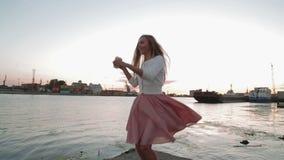 Προσοχή cofee ποτών γυναικών στον πηδώντας και χορεύοντας ποταμών λιμένα ηλιοβασιλέματος απόθεμα βίντεο