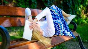 Προσπαθήστε να θυμηθείτε Τρυπώντας λογοτεχνία Η γυναίκα κούρασε το πρόσωπο παίρνει τη χαλάρωση σπασιμάτων στο βιβλίο ανάγνωσης κή στοκ φωτογραφίες