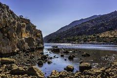 Προστατευμένο φυσικό λιμάνι όπως βλέπει πίσω από τους βράχους, πυροβολισμός χαμηλός, κάτω από τους σαφείς μπλε ουρανούς στοκ εικόνες