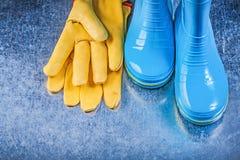 Προστατευτικά λαστιχένια γάντια δέρματος μποτών στο μεταλλικό υπόβαθρο GA Στοκ Φωτογραφίες