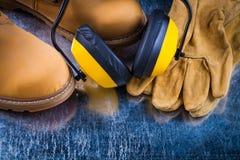 Προστατευτικά γάντια μποτών δέρματος και καλύμματα αυτιών μείωσης θορύβου επάνω Στοκ Εικόνα