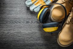 Προστατευτικά γάντια που λειτουργούν τα καλύμματα αυτιών μποτών στον ξύλινο πίνακα Στοκ Εικόνες