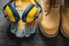 Προστατευτικά γάντια που λειτουργούν τα καλύμματα αυτιών μποτών δαντελλών στον ξύλινο πίνακα Στοκ Φωτογραφίες
