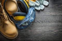 Προστατευτικά καλύμματα αυτιών προστατευτικών διόπτρων μποτών γαντιών στον ξύλινο πίνακα Στοκ Εικόνες