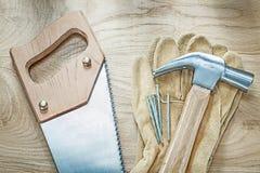 Προστατευτικά καρφιά γαντιών δέρματος σφυριών νυχιών handsaw στο ξύλινο BO Στοκ Φωτογραφία