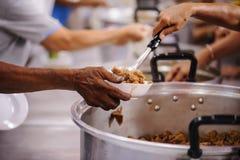 Προσφέρεται εθελοντικά τα τρόφιμα μεριδίου στους φτωχούς για να ανακουφίσει την πείνα: Έννοια φιλανθρωπίας στοκ φωτογραφία
