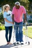 Προσφερθείτε εθελοντικά τη βοήθεια του ανώτερου ατόμου με το πλαίσιο περπατήματος Στοκ Φωτογραφία