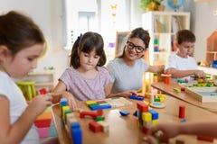 Προσχολικός δάσκαλος με τα παιδιά που παίζουν με τα ζωηρόχρωμα ξύλινα διδακτικά παιχνίδια στον παιδικό σταθμό στοκ εικόνες