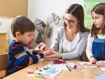 Προσχολικός δάσκαλος με τα παιδιά στον παιδικό σταθμό - δημιουργική κατηγορία τέχνης στοκ εικόνες
