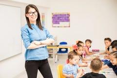 Προσχολικός δάσκαλος με τους σπουδαστές της στοκ φωτογραφία