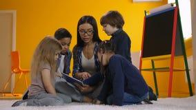 Προσχολικός δάσκαλος που διαβάζει ένα βιβλίο στα διαφορετικά παιδιά φιλμ μικρού μήκους