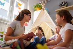 Προσχολικός δάσκαλος που διαβάζει μια ιστορία στα παιδιά στον παιδικό σταθμό στοκ φωτογραφία με δικαίωμα ελεύθερης χρήσης