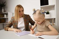 Προσχολικός στόχος γραψίματος κοριτσιών με τη μητέρα της στο γραφείο στοκ εικόνες