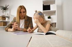 Προσχολικός στόχος γραψίματος κοριτσιών με τη μητέρα της στο γραφείο στοκ εικόνα με δικαίωμα ελεύθερης χρήσης