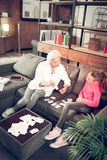 Προσχολικό κορίτσι που μελετά τις επιστολές με τη φροντίζοντας γιαγιά της στοκ φωτογραφίες