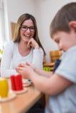 Προσχολικός δάσκαλος με το παιδί που αναπτύσσει τις δημιουργικές εκπαιδευτικές δραστηριότητες στοκ εικόνα