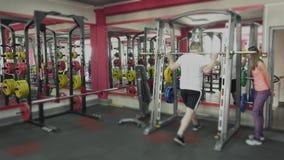 Προσωπική κατάρτιση με τον εκπαιδευτικό κοριτσιών για το άτομο με τη μεγάλη κοιλία στη γυμναστική Ο παχύς παχύσαρκος τύπος μαζί μ απόθεμα βίντεο