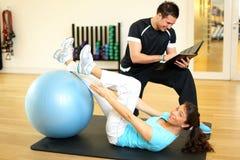 Προσωπικός εκπαιδευτής που καθοδηγεί τη γυναίκα στη γυμναστική στοκ εικόνα με δικαίωμα ελεύθερης χρήσης