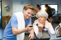 Προσωπικός εκπαιδευτής που παρουσιάζει χρόνο χρονομέτρων με διακόπτη στον ανώτερο πελάτη στοκ φωτογραφία