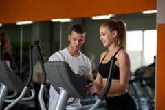 Προσωπικός εκπαιδευτής που συνεργάζεται με το θηλυκό πελάτη στη γυμναστική Στοκ Εικόνες
