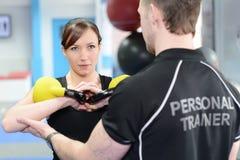 Προσωπικός εκπαιδευτής που βοηθά τη νέα γυναίκα με τα κουδούνια κατσαρολών Στοκ φωτογραφία με δικαίωμα ελεύθερης χρήσης