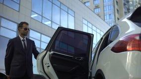 Προσωπικός οδηγός που περιμένει τον προϊστάμενο στο χώρο στάθμευσης, που βοηθά την για να πάρει στο αυτοκίνητο απόθεμα βίντεο
