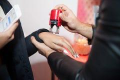Προσωπικό ασφαλείας που σφραγίζει το χέρι του φιλοξενουμένου που εισάγει τον τόπο συναντήσεως Στοκ Φωτογραφίες
