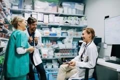 Προσωπικό νοσοκομείου που διοργανώνει την περιστασιακή συζήτηση στο φαρμακείο Στοκ φωτογραφίες με δικαίωμα ελεύθερης χρήσης