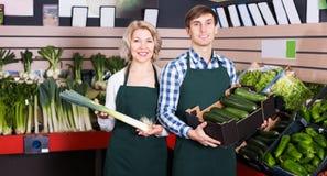 Προσωπικό παντοπωλείων που πωλεί τα φρέσκα λαχανικά στοκ φωτογραφία με δικαίωμα ελεύθερης χρήσης