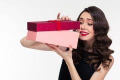 Προσδοκώμενη ελκυστική σγουρή γυναίκα στο αναδρομικό ύφος που ανοίγει το παρόν κιβώτιο στοκ εικόνες