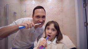 Προφορική υγεία, ευτυχής πατέρας με το κορίτσι παιδιών με τα δόντια βουρτσίσματος οδοντοβουρτσών μπροστά από τον καθρέφτη απόθεμα βίντεο