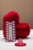 Προφορικό αντισυλληπτικό προφυλακτικό χαπιών στην κόκκινη καρδιά Στοκ Φωτογραφίες