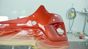 Προφυλακτήρας αυτοκινήτων μετά από να χρωματίσει σε έναν θάλαμο ψεκασμού αυτοκινήτων Προφυλακτήρας χρώματος κερασιών οχημάτων στοκ εικόνες