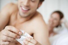 Προφυλακτικό ανοίγματος ανδρών με τη γυναίκα στο κρεβάτι Στοκ Εικόνες