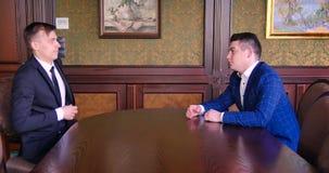 Προϊστάμενος δύο ο νέος επιχειρηματιών κάθεται στο τραπέζι των διαπραγματεύσεων Διαπραγματευτείτε, συμβιβάστε, τινάξτε τα χέρια,  φιλμ μικρού μήκους