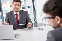 Προϊστάμενος με τα έγγραφα που εξετάζει το συνάδελφο στην επιχειρησιακή συνεδρίαση Στοκ Φωτογραφία
