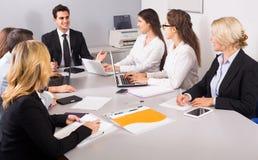 Προϊστάμενος με τους επαγγελματικούς ανώτερους υπαλλήλους που συζητούν προετοιμάζοντας τη σύμβαση Στοκ φωτογραφία με δικαίωμα ελεύθερης χρήσης