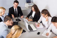 Προϊστάμενος με τους επαγγελματικούς ανώτερους υπαλλήλους που συζητούν προετοιμάζοντας τη σύμβαση Στοκ Εικόνα