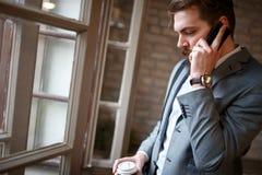 Προϊστάμενος στην επιχείρηση που μιλά στο τηλέφωνο κυττάρων με το συνέταιρο Στοκ Φωτογραφία